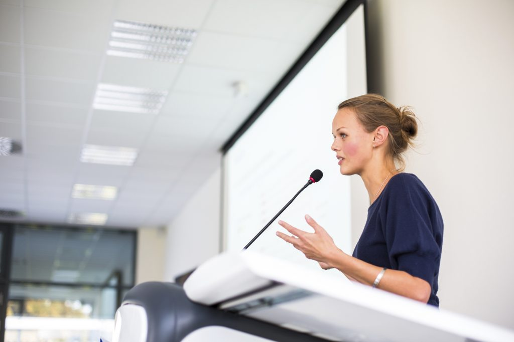 Pretty, young business woman giving a presentation in a conferen