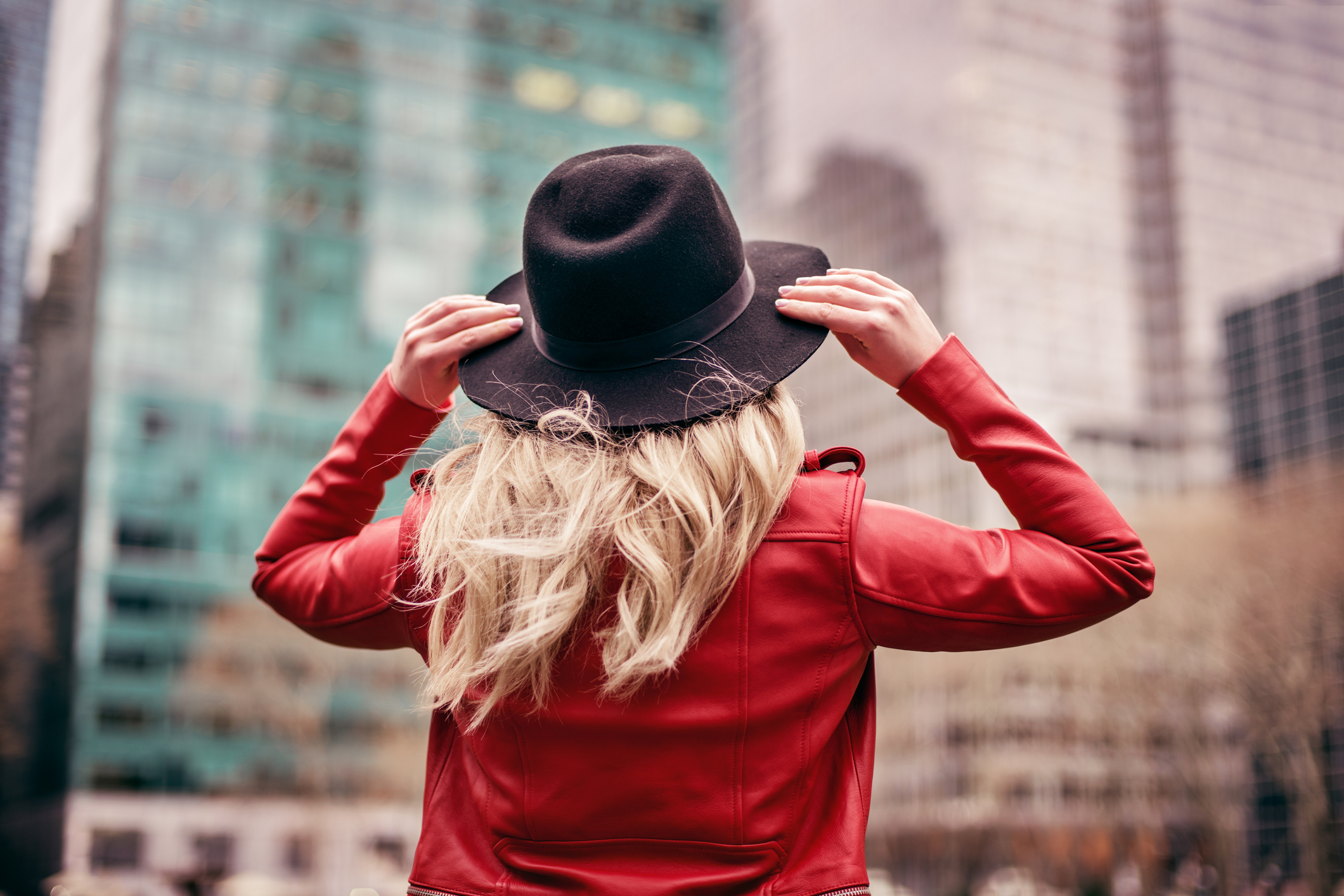 young woman wearing hat walking on streets of New York