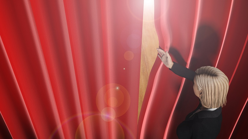 woman looking through theatre curtains on stage